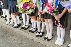 Dziewczyny szkoła podstawowa z bukietami kwiaty w jego rękach Buty na jej pantyhose, skarpetach i pończochach cieków i białych, Fotografia Stock