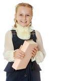 Dziewczyny szkoła w czarnej książce w jego i sukni ręki Fotografia Stock