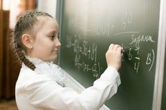 Dziewczyny szkoły podstawowej żeński uczeń pisze na blackboard zdjęcie stock