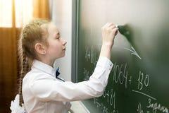 Dziewczyny szko?y podstawowej ?e?ski ucze? pisze na blackboard fotografia stock