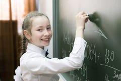 Dziewczyny szko?y podstawowej ?e?ski ucze? pisze na blackboard zdjęcia royalty free