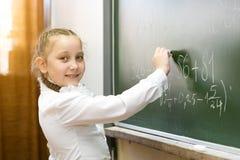 Dziewczyny szko?y podstawowej ?e?ski ucze? pisze na blackboard obrazy stock