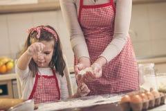 Dziewczyny tryskaczowa mąka na kuchennym kontuarze zdjęcia stock