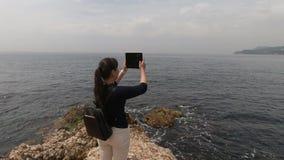 Dziewczyny turystyczna pozycja na skalistej krawędzi i wp8lywy na kamerze pastylki piękny morze zbiory