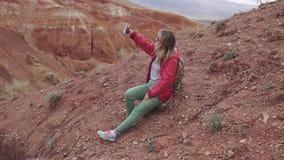 Dziewczyny turystyczny robi selfie na kamery smartphone czerwone góry i czerwieni ziemia na Mars jak zdjęcie wideo