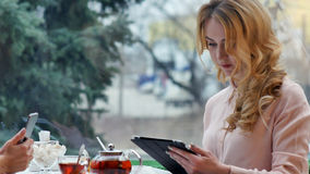 Dziewczyny używają ich przerwę od pracy pić kawę i używać cyfrową pastylkę, gadka Fotografia Royalty Free