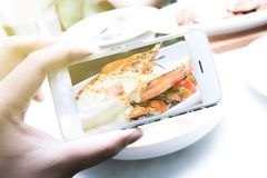 Dziewczyny używają smartphones, biorą obrazki jedzenie w restauracjach zdjęcie stock