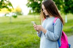 Dziewczyny uczennicy nastolatek ręki barwiona ilustracja zrobił natury lato W rękach trzyma smartphone Za plecakiem Pisze wiadomo Zdjęcie Stock