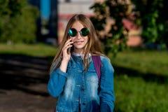 Dziewczyny uczennicy nastolatek W lecie w mieście W jego rękach trzyma smartphone W cajgach odziewa, okulary przeciwsłoneczni Opo obrazy stock