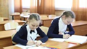 Dziewczyny uczennicy zerknięcie each inny w notatniku zdjęcie wideo