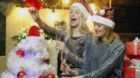 Dziewczyny w Bożenarodzeniowych kapeluszach dekorują choinki i napoju szampana na tle Bożenarodzeniowe dekoracje nowy zbiory
