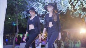 Dziewczyny w czarnych kapeluszach i trouser kostiumach z nagimi żołądkami chodzą puszka wybieg w modny cukierniany plenerowym zbiory wideo