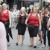 Dziewczyny w czerwonych koszulkach chodzą na ulicie przy karmazynki przyjęciem Zdjęcie Stock