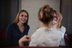 Dziewczyny w kawiarni Jeden dama siedzi z powrotem kamera Kobiety przyjaźnie i czasu wolnego pojęcie obrazy royalty free