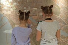 Dziewczyny w muzealnym słuchaniu ciekawa informacja o eksponacie przez hełmofonów mapa interaktywny zdjęcie stock