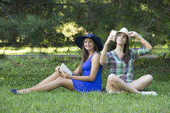 Dziewczyny w parku z książką i telefonem komórkowym Zdjęcia Royalty Free