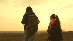 Dziewczyny w podwy?ce kobiety podróż z plecakiem przy zmierzchem Turyści matka i dziecko iść zmierzch Poj?cie zdjęcie wideo
