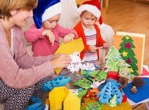 Dziewczyny w Santa kapeluszach i uśmiechniętej mamie robi aplikacyjnej pracie Fotografia Royalty Free