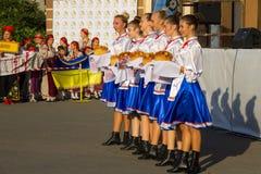 Dziewczyny w ukraińskiej tradycyjnej odzieży przygotowywają mile widziany gość Fotografia Stock