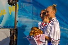 Dziewczyny w ukraińskiej tradycyjnej odzieży przygotowywają mile widziany gość Zdjęcia Stock
