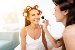 Dziewczyny w włosianych curlers reżyserowali dnia zdrój i robić makijażowi Zakończenie fotografia dziewczyny robi makijażowi Obrazy Stock
