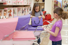 Dziewczyny w zabawkarskim sklepie nabywali torebkę i powozika zdjęcia stock