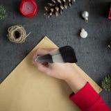 Dziewczyny writing list Santa z atramentu piórem na koloru żółtego papierze na popielatym tle z boże narodzenie dekoracjami Zdjęcia Royalty Free