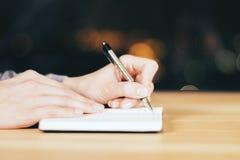 Dziewczyny writing w dzienniczku na drewnianym stole przy nocą obraz royalty free