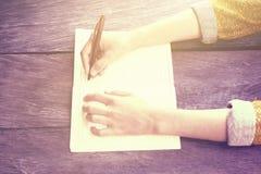 Dziewczyny writing z piórem w pustym dzienniczku na drewnianym stole, instagram Obrazy Royalty Free