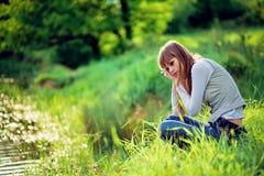 dziewczyny z dokładnością do jeziora trawy posiedzenia zdjęcie stock