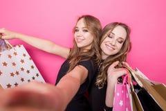 Dziewczyny z torba na zakupy bierze selfie z ich telefonem komórkowym Zdjęcia Royalty Free