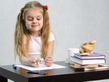 Dziewczyny zamyślenie i bezwysiłkowo obraca szklaną kulę ziemską, siedzi przy stołem w wizerunku pisarz Zdjęcia Stock