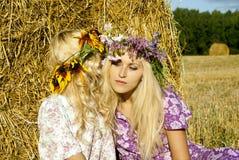 Dziewczyny zbliżać haystacks Zdjęcia Royalty Free