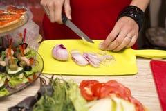 Dziewczyny znakomicie - siekać cebule na żółtej tnącej desce fotografia stock