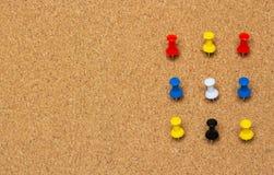 Dziewięć barwiący przypięty guzik na korkowej desce fotografia stock