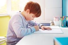 Dziewięć lat dziecko pisze w domu zdjęcie stock