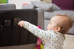 Dziewięć miesięcy starej dziewczynki chwyta pilot do tv Zdjęcie Stock