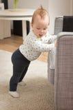 Dziewięć miesięcy starej dziewczynki pozyci na jej ciekach Fotografia Stock