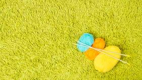 Dziewiarskiej przędzy piłki, igły nad zielonym dywanowym tłem Zdjęcia Royalty Free