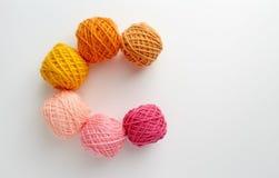 Dziewiarskiej przędzy piłki w menchiach i żółtym brzmieniu Fotografia Stock