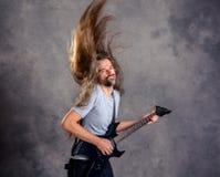 Dziki muzyk z czarnym gitary i latania włosy Zdjęcia Royalty Free