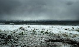 Dziki niebo nad morze z śniegiem na plaży Obrazy Stock