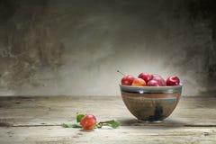 Dzikie czerwone śliwki w ceramicznym pucharze na starym drewnianym stole Fotografia Stock
