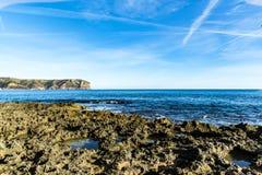 Dzikie fale łama przeciw skałom przy seashore fotografia stock