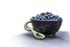 Dzikie lasowe czarne jagody w łyżkowym i glinianym pipkin naczyniu z białą rękojeścią Zdjęcia Royalty Free