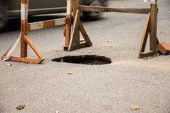 Dziura w asfalcie na automobilowej jezdni ulicie Jama w drogowej powierzchni, otacza budować płotową budowę z ostrzegawczą taśmą Obraz Stock