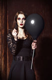 Dziwaczna okaleczająca dziewczyna przebija balon igłą Zdjęcie Stock