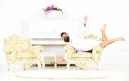 Dziwaczny mężczyzna pozuje w karle Dziwny faceta lying on the beach na antykwarskim meble Milioner w białym pokoju hotelowym obrazy royalty free
