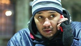 Dziwaczny mężczyzna w podławym odziewa opowiadać nad telefonem, patrzeje wokoło podejrzliwie zbiory wideo