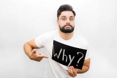 Dziwaczny młody człowiek pokazuje emocję na twarzy i patrzeje kamerę Trzyma polate z pisać słowem Dlaczego Także wskazuje zdjęcie stock